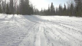 El viento levanta la nieve acumulada por la ventisca sobre pista con los rastros de la moto de nieve almacen de metraje de vídeo