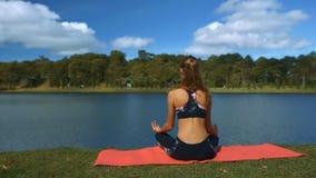 El viento sacude la cola de caballo de la muchacha en actitud de la yoga por el río