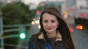 El viento sopla a mujeres jovenes hermosas del pelo largo muchacha sonriente que se coloca en el puente por la tarde y las mirada Imagen de archivo libre de regalías