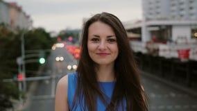El viento sopla a mujeres jovenes hermosas largas del pelo oscuro muchacha feliz, sonriente que se coloca en el puente y miradas  Foto de archivo