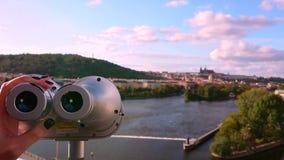El viento sopla el pelo marrón de una muchacha que mire con los prismáticos a la ciudad vieja entera de Praga, en el tejado de a almacen de video