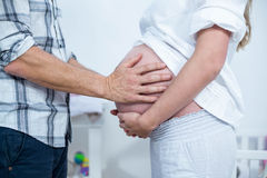 El vientre conmovedor de la mujer embarazada del hombre Foto de archivo