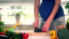 El vientre de la mujer embarazada y las manos afilan el cuchillo de cocina en la tabla almacen de video