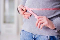 El vientre de medición de la mujer embarazada con centímetro Foto de archivo libre de regalías
