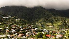 El villlage debajo de la montaña con el cielo nublado imagenes de archivo
