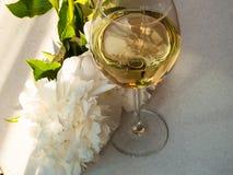 El vino blanco en el vidrio y la peonía florece Cena romántica Imagen de archivo