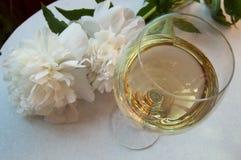 El vino blanco en el vidrio y la peonía florece Cena romántica Fotos de archivo