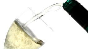 El vino blanco vertió en el vidrio de la botella en el fondo blanco almacen de video
