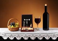 El vino en la botella, los accesorios para el vino de apertura y las uvas Imagenes de archivo