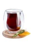 El vino en un vidrio no es la forma usual Wine en un vidrio en un soporte de madera adornado con romero y una rebanada anaranjada Imágenes de archivo libres de regalías