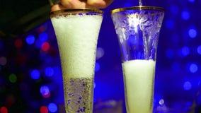El vino espumoso se vierte en los vidrios En el fondo, las luces del bokeh y las guirnaldas del abeto de la Navidad almacen de video