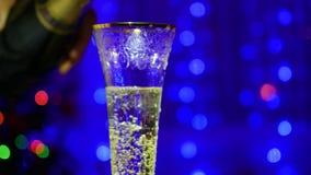 El vino espumoso se vierte en los vidrios En el fondo, las luces del bokeh y las guirnaldas del abeto de la Navidad metrajes