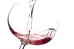 El vino a fluir en un vidrio foto de archivo
