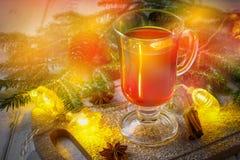 El vino reflexionado sobre del Año Nuevo en un vidrio en el fondo de ramitas, de velas y de guirnaldas Fotografía de archivo libre de regalías