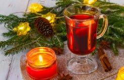 El vino reflexionado sobre del Año Nuevo en un vidrio en el fondo de ramitas, de velas y de guirnaldas Foto de archivo