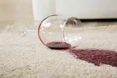 El vino rojo desbordó el vidrio en la alfombra Foto de archivo