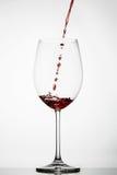 El vino rojo salpica en un vidrio Foto de archivo