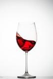 El vino rojo salpica en un vidrio Imagenes de archivo