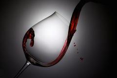 El vino rojo vertió en una copa de vino con descensos Imagen de archivo libre de regalías