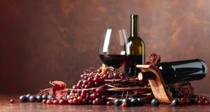 El vino rojo y las uvas frescas con secado encima de vid se va imagen de archivo
