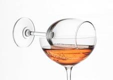El vino rosado de encendido en la composición del vidrio de la copa de vino y de cóctel creativa Foto de archivo libre de regalías