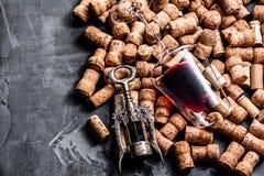 El vino tapa el contexto del fondo y la copa de vino del fondo con corcho imagen de archivo