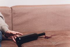 El vino tinto se derramó en un sofá marrón del sofá la botella oscura de vino tinto cayó fotografía de archivo libre de regalías