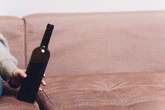 El vino tinto se derramó en un sofá marrón del sofá la botella oscura de vino tinto cayó foto de archivo