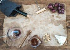 El vino y el aperitivo fijaron con el espacio de la copia en el centro Vidrio de vino rojo, botella, corkscrewer, queso verde, uv Fotografía de archivo