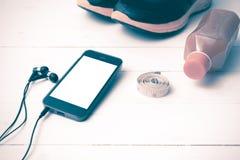 El vintage de las zapatillas deportivas, del zumo de naranja, de la cinta métrica y del teléfono entona Imágenes de archivo libres de regalías