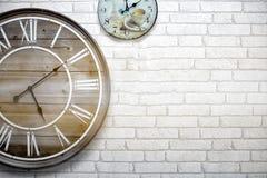 El vintage del reloj de pared se cuelga en una pared de ladrillo blanca, diciendo el tiempo exactamente fotos de archivo