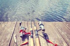 El vintage entonó la imagen del equipo de pesca en un embarcadero de madera Fotos de archivo