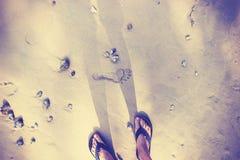 El vintage entonó pies femeninos en chancletas en la arena Foto de archivo libre de regalías