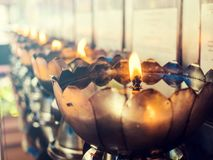 El vintage filtró en las lámparas de aceite, tenedor de plata de la forma del loto en templo asiático Fotos de archivo libres de regalías