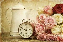 El vintage texturizó vida inmóvil con las rosas y el despertador fotos de archivo libres de regalías