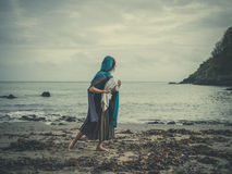 El vintage tiró de mujer en la playa con el bebé Foto de archivo libre de regalías