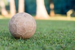 el vintage utilizó el balón de fútbol que mentía en la hierba en parque, en la sombra Los árboles en el fondo están en el sol, Ri Imagenes de archivo