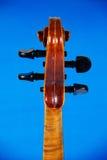 El violín del fingerboard en un fondo azul fotos de archivo