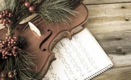 El violín del vintage adornó con el helecho de la Navidad que mentía en partitura Foto de archivo libre de regalías