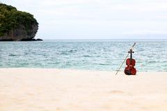 El violín en la playa arenosa blanca por el mar Fotos de archivo libres de regalías