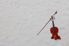 El violín en la playa arenosa blanca por el mar Fotos de archivo
