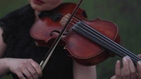 El violinista de la mujer toca el violín en prado en la oscuridad almacen de video