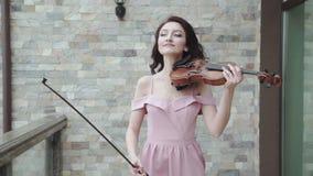 El violinista de sexo femenino confiado camina en vestido de noche que sopla, y juegos en el violín almacen de video