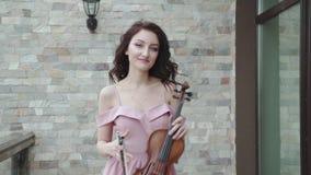 El violinista de sexo femenino elegante camina en vestido de noche que sopla, y juegos en el violín metrajes