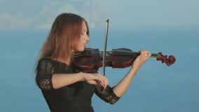 El violinista hermoso en vestido del tracery juega en a almacen de metraje de vídeo