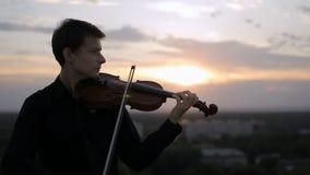 El violinista pone el instrumento musical en su hombro y comienza a jugar almacen de video