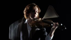 El violinista realiza un violín en un estudio negro Fondo negro metrajes