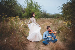 El violinista y la mujer en el vestido blanco, hombre joven juega en el violín la naturaleza del fondo Fotografía de archivo