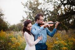 El violinista y la mujer en el vestido blanco, hombre joven juega en el violín la naturaleza del fondo Fotos de archivo libres de regalías