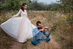 El violinista y la mujer en el vestido blanco, hombre joven juega en el violín la naturaleza del fondo Foto de archivo libre de regalías